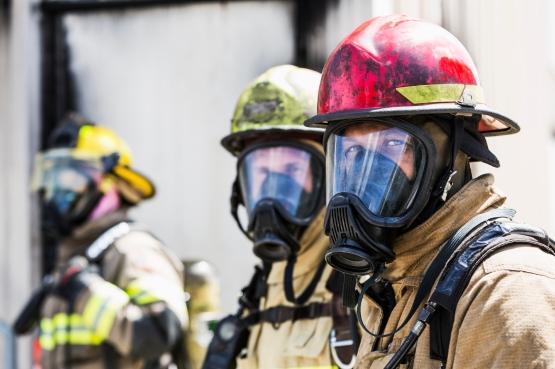 Three firefighters wearing oxygen masks