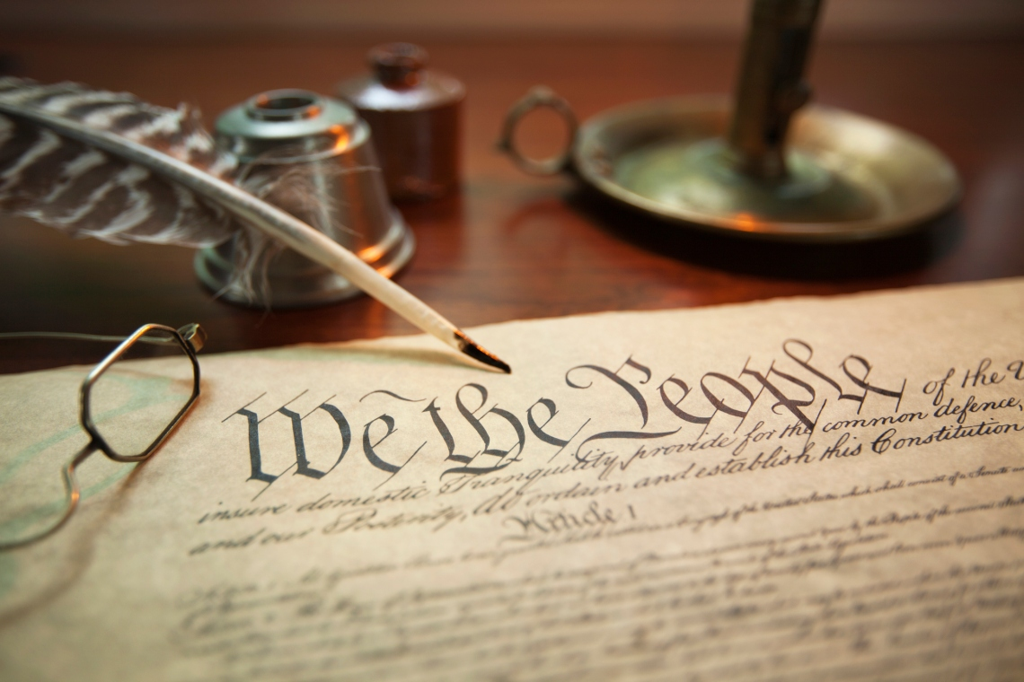 United States Constitution with quill, glasses and candle holder