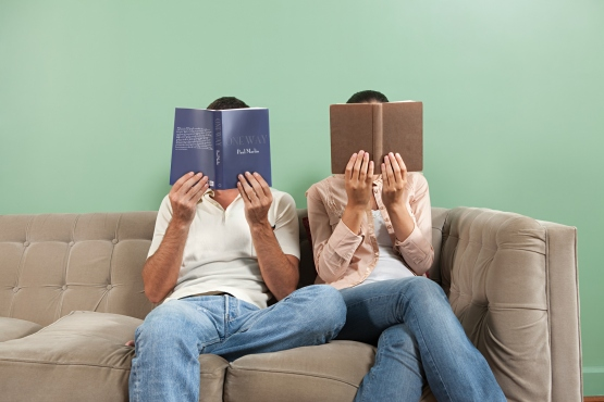 Young couple reading with books obscuring faces